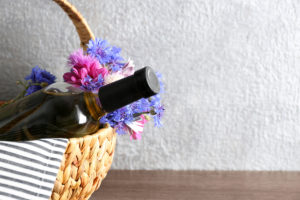 Wine bottle with flowers in basket on light background